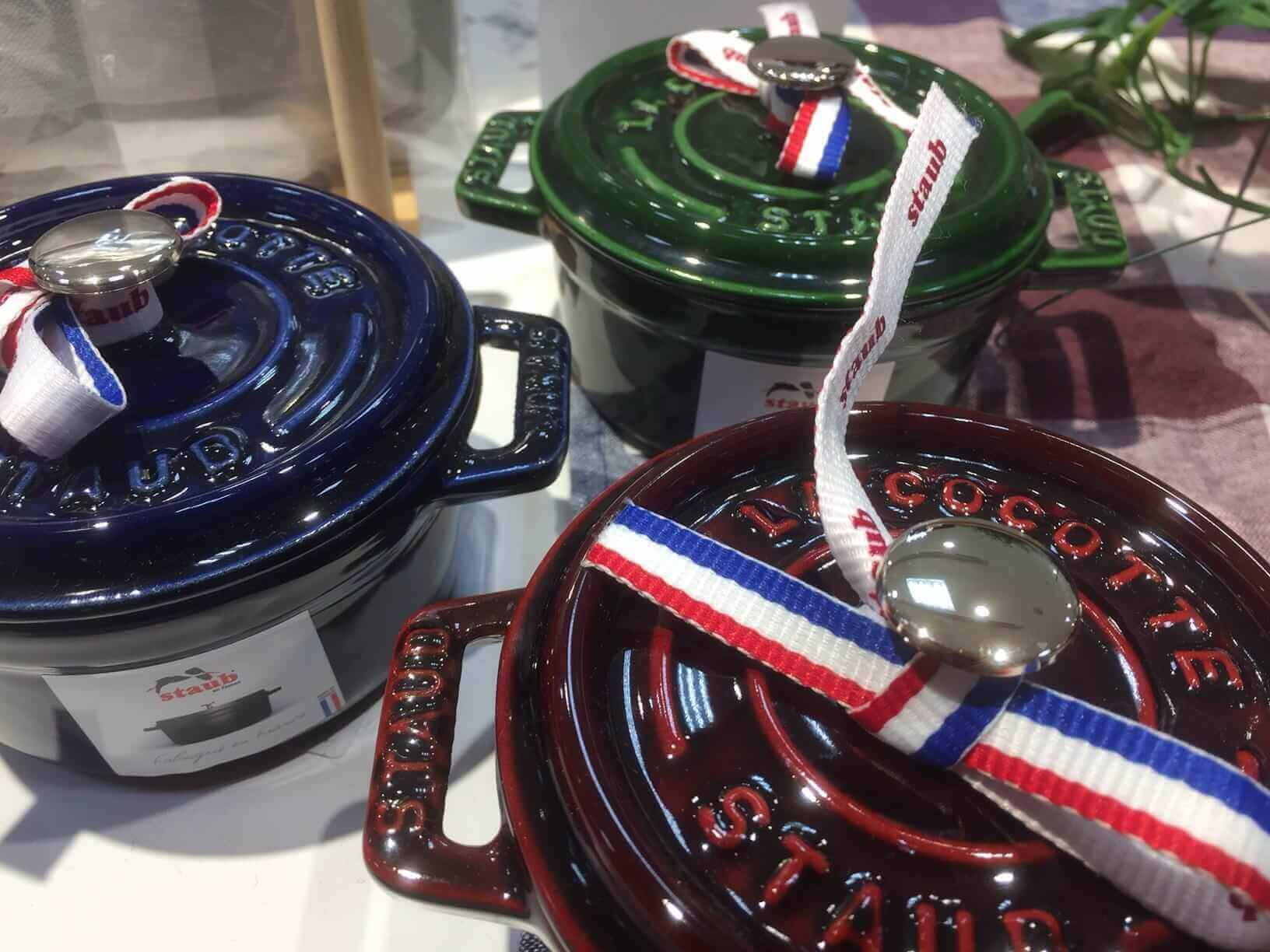 Display of Staub pot. they feature high gloss enamel and a made in France ribbon. (picture of three Staub pots, one is red the other is blue and the last is green)