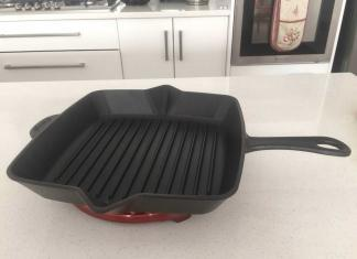 Black Staub grill pan on cherry red Staub trivet.