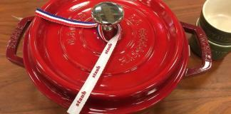 New Red Staub Dutch oven on a wooden table.
