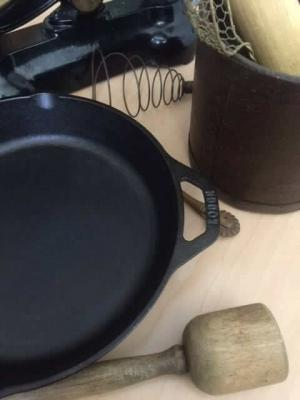 What are the benefits of cooking with cast-iron. In the picture is a cast iron skillet on a table along with antique kitchenware.