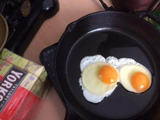 Two eggs cooking in a cast iron skillet. Find out the benefits of cooking with cast iron.