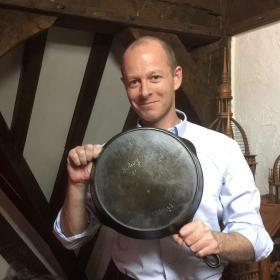 Sidney Hollow Ware Co. made fine cast iron cookware. in the picture is a man holding a cast iron skillet.