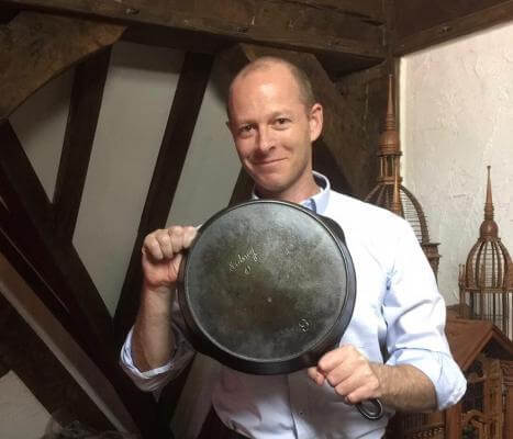 Sidney Hollowware Co made fine cast iron cookware. in the picture is a man holding a cast iron skillet.