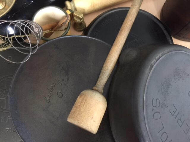 Why use cast iron skillets. Four vintage cast-iron skillets on a wooden table.