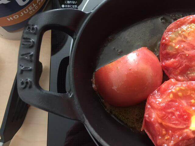 The benefits of enamel cast-iron. In the picture are tomatoes cooking in a Staub stackable dish.