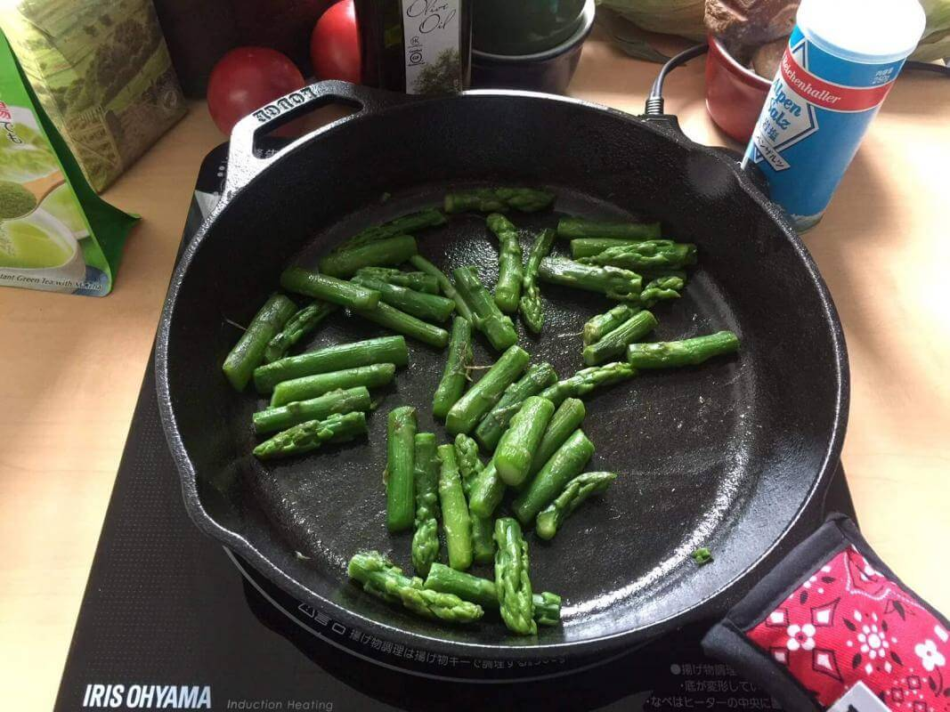 Cooking asparagus cooking in a cast iron skillet made by Lodge.