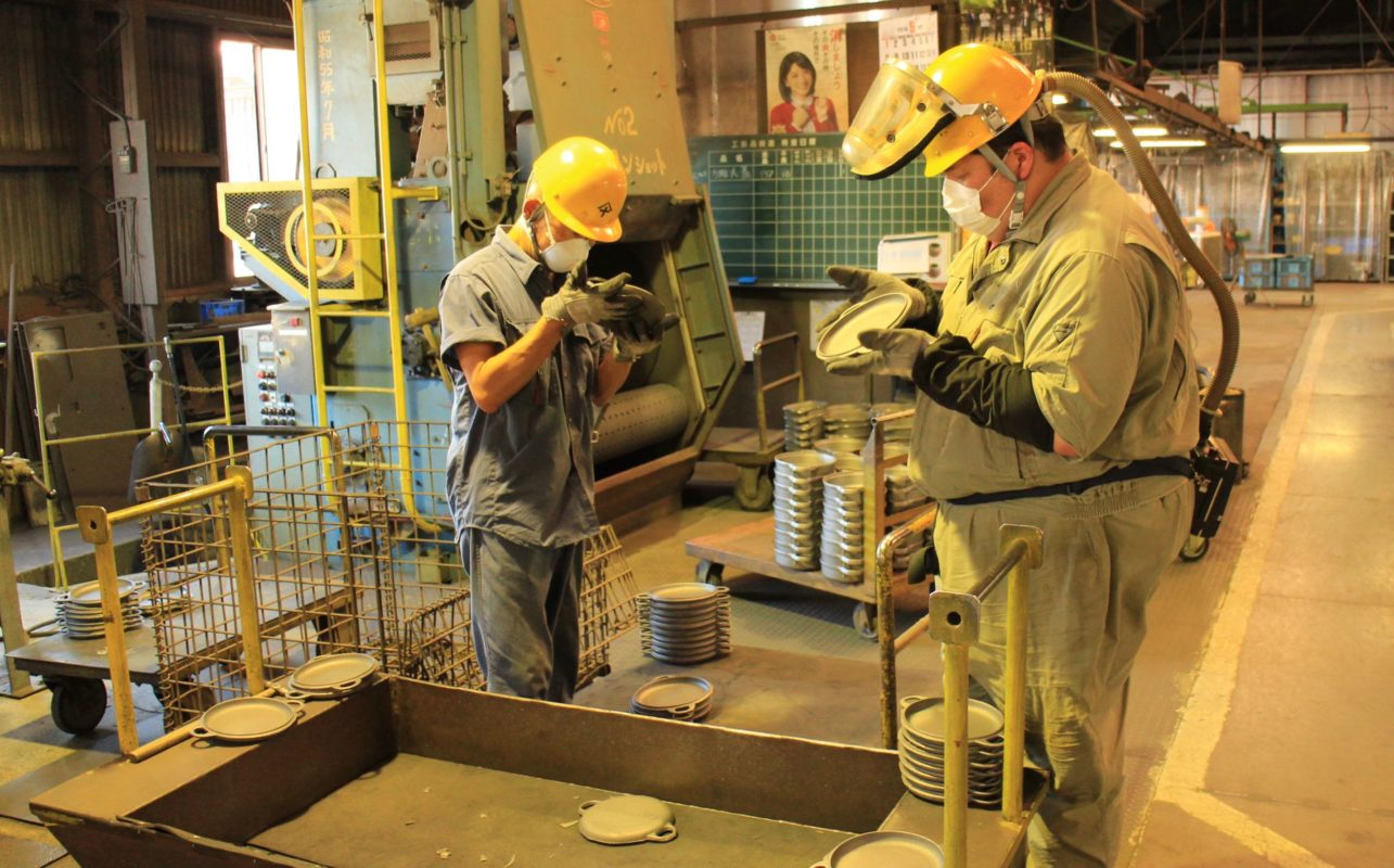 Two Oigen foundry workers inspecting cast-iron for imperfections.