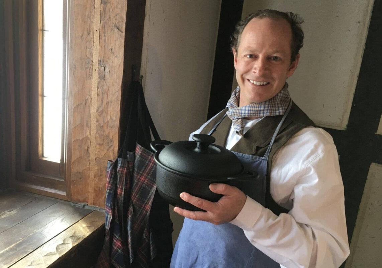Brett Standeven a.k.a. Boonie Hicks holding a cast iron Dutch Oven.